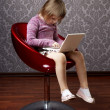 Girl sitting in a chair with a laptop — Stock Photo #7617275