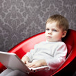 Boy sitting in a chair with a laptop - Foto Stock