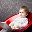 Boy sitting in a chair with a laptop - Stock Photo