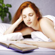 Woman who reads a book in bed - Stock Photo