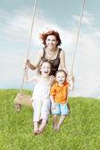 Familie schwingen gegen den himmel und gras — Stockfoto