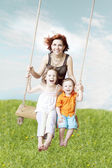 Family swing against the sky and grass — Stok fotoğraf
