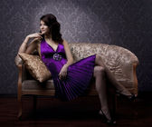 Luxurious woman sitting on a gold vintage couch — Stock fotografie