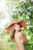 Beautiful half-naked woman among flowering gardens — Stok fotoğraf