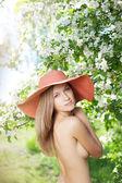 Krásná polonahá žena mezi kvetoucí zahrady — Stock fotografie