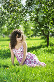 Beautiful girl in the flowered garden — Stock Photo