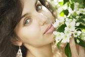 Beautiful girl in the flowered garden — Stock Photo