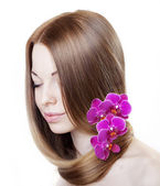 Beautiful girl with orchids in her gorgeous hair — Stock Photo