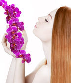 Beautiful girl with orchids — Stock Photo