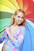 Beautiful pregnant girl with a rainbow umbrella — Stock Photo