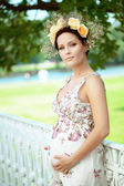 Beautiful pregnant girl with a wreath of flowers — Stock Photo
