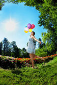 Woman with balloons on grass — Stock Photo
