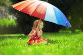 Little girl with a rainbow umbrella in park — Stok fotoğraf