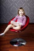 Flickan sitter i en stol med en bärbar dator — Stockfoto