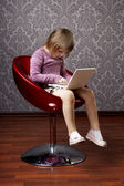 Girl sitting in a chair with a laptop — Stock Photo