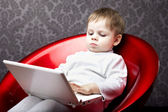 Boy sitting in a chair with a laptop — Stock Photo