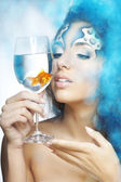 Girl with makeup, with a fish in a glass in her hand — Stock Photo