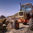 Old, rusty tractor on a pebble beach — Stock Photo