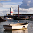 Stock Photo: Small Boat tied in harbour with Lighthouse