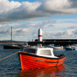Small Fishing Boat tied in a harbour with Lighthouse — Stock Photo #7476844