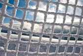 Frysta mesh staket med blå himmel i bakgrunden — Stockfoto