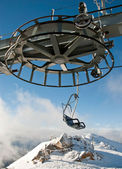 Double ski lift and the wheel with moutain — Stock Photo