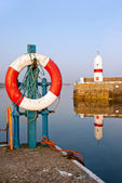 White and Red Life Buoy in Harbour with Lighthouse — Stock Photo