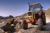 Stará, rezavá traktor na oblázkové pláži — Stock fotografie