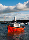 Small Fishing Boat tied in a harbour with Lighthouse — Stock Photo