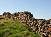 Viejo muro de piedra con hierba verde y el azul cielo — Foto de Stock
