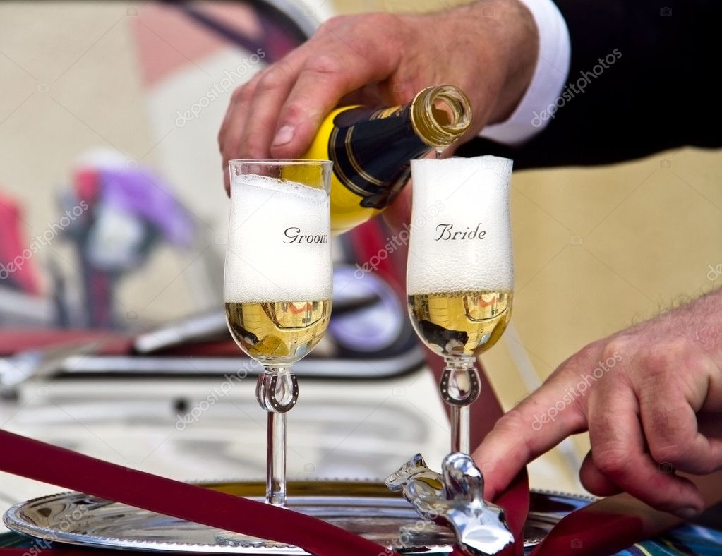 Wedding - Pouring Champagne to Groom and Bride Glasses on a Silver Plate — Stock Photo #7476368