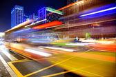De alta velocidad y senderos luz borrosa del autobús en el centro — Foto de Stock