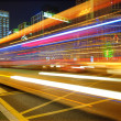 High speed and blurred bus light trails in downtown nightscape — Stock Photo #7486877