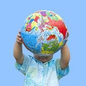 Boy holding the earth model under blue sky — Stock Photo