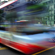High speed and blurred bus trails on downtown road - Stock Photo