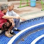 A senior couple sitting beside a pool — Stock Photo
