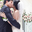 A young couple embracing and kissing on their wedding day — Stock Photo