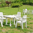 White chair and table on green lawn - Stock Photo