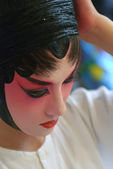 A chinese opera actress is painting her face — Stock Photo