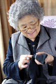 Sewing grandmother — Stock Photo
