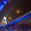 Bright lights under urban overpass - Stock Photo
