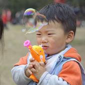 Child blowing soap bubbles — Stock Photo