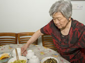 The grandmother is preparing dinner — Stock Photo