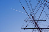 Ship mast with airplane trace on background — Stock Photo