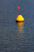 Yellow buoy and red flag — Stock Photo