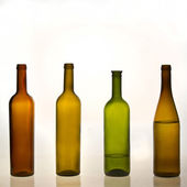 Colored bottles with and without water — Stock Photo