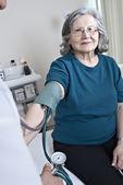 Doctor measuring mature patient blood presure — Stock Photo