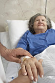 Adult helping senior in hospital — Stock Photo