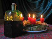 A christmas wreath with burning candles and an antique bottle of wine — Stock Photo