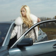 Glamorous blond babe near tuned super car — Stockfoto